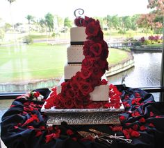 White wedding cake with cascading red roses