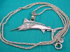 This fun sterling silver swordfish pendant is poised in flight! The highly detailed swordfish is suspended from a sterling silver braided