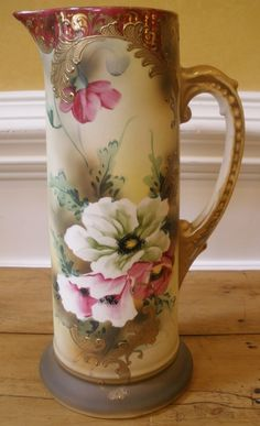 Beautiful antique porcelain tall tankard, hand painted with pink and white flowers surrounded by green foliage and accented with raised gold scroll