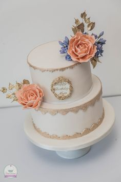 Gold and white cake with handmade peach-coloured roses, gold leaves and lilac freesia's.