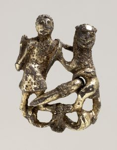 A ring brooch formed of two interlocking figures. A male figure in a short tunic with a kite-shaped shield strapped over his shoulder defends himself with a club against an attacking lion. The details of the hair, tunic and the lion's fur are rendered by small punches. The figures stand on a foliate base. 13thC (Europe,United Kingdom,England,Northamptonshire)