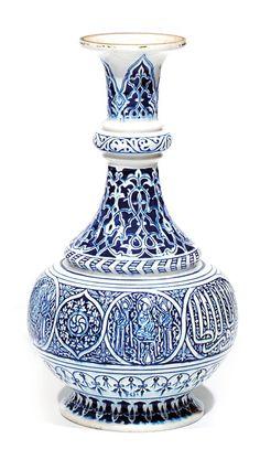 THéODORE DECK. Vase en faïence, dans le style Mamluque (XIV-XVe siècle), à décor en léger relief crème sur fond bleu nuit de personnages et caractères coufiques dans des médaillons. La base est ornée de lambrequins. Monogrammé THD sur le pied. (Le fond du vase reconstitué). France, vers 1880.