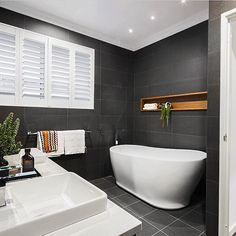 White round curved freestanding bathtub, white bench top vanity with white square basin, chrome tap and mixer, charcoal tiled floor and walls with timber niche. Project by - @crib_creative #taps #interiordesign #bathroom #australia #architecture #bathroomdesign #bathroomcollective Visit our website for more www.bathroomcollective.com.au