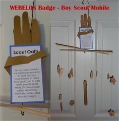 Webelos Badge. Artist Mobile.  We had the boys trace their own hands to make the Boy Scout Sign. The 12 dangling shapes list the points of the Scout Law. The big popsicle stick has the Scout motto and slogan. On the back of the hand a printout of the Outdoor Code. All required for Webelos badge and to be memorized for Arrow of Light.