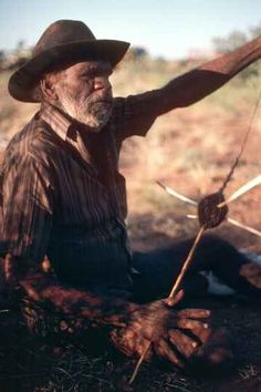 A Warlpiri man makes hairstring, using a spindle;