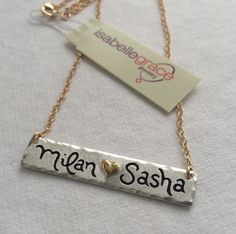 """Double Name Bar Necklace - Get 25% OFF with code """"VP25"""". A gorgeous Valentine's Day gift for her, this is the perfect piece to layer with a longer necklace! The Double Name Bar Necklace features a (0.999) fine silver bar custom inscribed with two names or sets of initials separated by a 22kt gold heart. The edges are also slightly hammered to give it a distressed look. The name bar is approximately 1 3/4 inches long but the size may vary depending on personalization. Also has a matte finish!"""