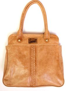 A structured bag with a little bit of ease in the natural color and braiding. I love the combo. The Freedom bag from Elf.