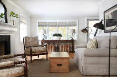 Cottage living room features a pair of seagrass baskets tucked under a long farmhouse console ...
