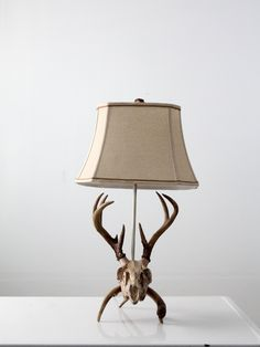 This is a vintage deer skull table lamp. A deer skull with antlers shapes the base of the lamp. It features a metal harp with a natural tone lamp shade and a horn finial. - deer skull with antlers sha