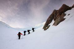 Hikers trekking through snow in Hjrundfjorden, Norway