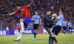 Alexis Sanchez of Chile heads to score a goal as teammate Arturo Vidal challenges with Uruguay\'s Cristian Rodriguez during their friendly soccer match in Santiago