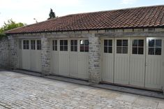 Wooden bi-fold garage doors with draught excluded frames are ideally suited for a climate controlled garages. These folding garage doors are also available as bespoke doors. Garage Doors Uk, Custom Garage Doors, Wooden Garage Doors, Garage Exterior, Custom Garages, Garage House, Exterior Doors, House Front, Small Garage