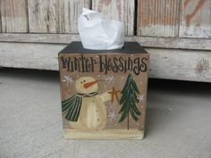 Primitive Snowman Winter Blessings Hand Painted Tissue Box Cover. This is a great tissue box cover to accent your winter decor. You can choose your side color and the snowmans scarf color. Shown in black with a hunter green scarf. Ive hand painted on this snowman next to a pine tree and the saying Winter Blessings. Sturdy paper mache, sealed for easy dusting. Holds boutique style tissue boxes. Size is 5x5. Hand painted, designed and signed by Heidi.