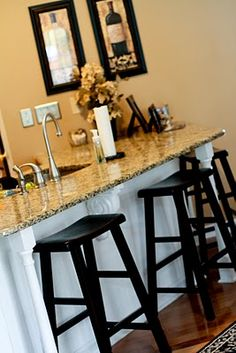 Great kitchen island/bar -- granite counter, white with corbels and newel post furniture legs, black kitchen stools