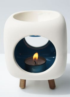 A handmade ceramic wax warmer. Can be used with/without wooden legs.  Check out our soy melt: