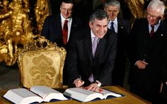 British Prime Minister Gordon Brown, foreground, signs the EU's Lisbon Treaty at the Museu dos Coches (Carriage Museum) as President of the ...