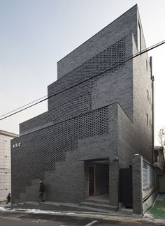 Perforated brick walls front this Seoul office block. Also just cool looking