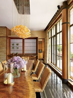 A light fixture conceived by De la Torre, featuring glass spheres commissioned from a Venetian workshop, hangs above a bubinga-slab dining table by Peter Superti from Mark McDonald and custom-made chairs; the hurricane lamps are by Ralph Lauren Home.