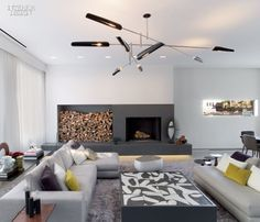 In the living area of a sprawling New York penthouse apartment by Steve E. Blatz Architect, Rodolfo Dordoni sofas and a Patricia Urquiola ottoman gather beneath a David Weeks chandelier, near a. Living Room Interior, Home Living Room, Living Area, Living Spaces, Interior Design Magazine, Modern Fireplace, Fireplace Design, Grey Fireplace, Interior Inspiration