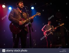 Male guitarist and bassist in a band on stage at a concert. Stock Photo