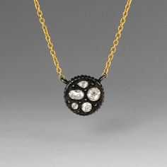 An oxidized gilver mosaic disc with rose cut diamonds= 0.65cttw on an 18k yellow gold chain by Yossi Harari