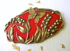 An enamel red brooch, Art Nouveau and gold floral relief....antique:  This is a lovely and graceful antique brooch thats oval shaped with rich red enamel and raised gold-tone butterfly and flower relief. It has a c clasp. A unique piece for the collectors.  Length ... 2-1/2 Width .... 1-1/2 Hallmark .... none Condition .... Very good with some tiny enamel spotting (see photos)  Vintage items may show the passage of time, but this is integral to their charm. All gently used with very little…