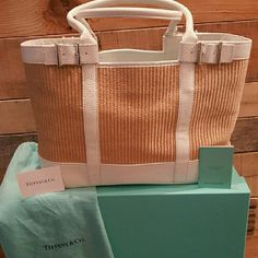 "🎉HP 7/8/16🎉NEW""RARE"" T&CO.STRAW LARGE TOTE 🎉HP 7/8/16 BEST IN SWIM🎉 ✔PRICE DROP✔ NEW TIFFANY & CO.TOTE WHITE LEATHER POSH TAKES 20%  DETAIL WITH STRAW SIDES SIZE LARGE BRAND NEW IN BOX & DUSTBAG SOLD OUT IN STORES TIFFANY BLUE SILK INNER LINING AND DETAIL ON HARDWARE 2 DEEP POCKETS WITH ZIPPER POCKET IN CENTER INSIDE SIDE INSIDE ZIPPER POCKET AS WELL 3 SMALLER POCKETS ON OPPOSITE SIDE INSIDE GREAT BEAUTIFUL BAG!!! COMES WITH DUST BAG AND BOX MUST HAVE!!! *NO RETURNS ON PURCHASE ASK…"