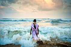 A young woman stands in the surf during sunset at Marina Beach in Chennai, India. Marina beach is the second longest stretch of beach in the world, measuring 2.5 miles long.