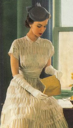 1950's Fashion.  Notice, she has her gloves on.  Beautiful Dress.