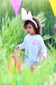 Eggsellent day out: North fills her Easter basket while wearing bunny ears for an egg hunt...