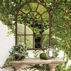 Outdoor mirror styled with lanterns and a stone credenza