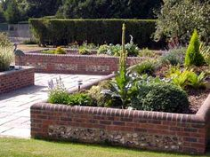 trendy backyard deck on a hill raised beds Raised Flower Beds, Raised Beds, Brick Wall Gardens, Patio Wall, Colorful Plants, Landscaping With Rocks, Brickwork, Garden Pots, Garden Walls
