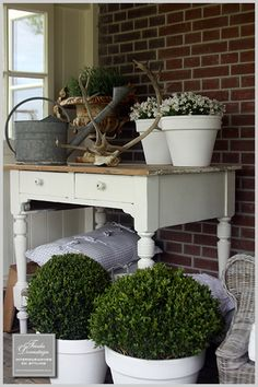 love the clay pots painted white contrasted with the preserved greens