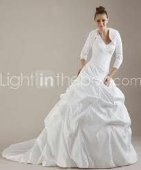 White ballgown with pickups in the skirt and a long-sleeved shrug.