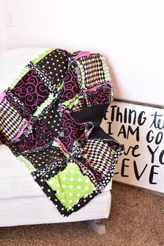 A fun whimsical baby girl rag quilt made in pink, green, black. measures 44x44 inches