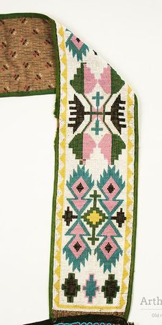 """An 1880's Ojibwe bandolier bag with a loom beaded strap and panel with a spot stitched panel between them. The loom beaded panel and straps all have white beaded backgrounds. The bag'c panel has an abstract floral design in an """"X"""" pattern and the two panels of the strap each have different designs, both elements more commonly seen on Ojibwe bags. The straps, which are outlined in green binding, are attached to a panel of dark blue wool trade cloth which extends the length or the two panels…"""