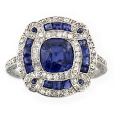 An Art Deco sapphire and diamond ring, the cushion-cut sapphire, estimated to weigh 1.7 carats, to the centre of a fancy cluster surround of a brilliant-cut diamond-set eight figure-of-eight design, embellished with calibre-cut sapphires, all within a brilliant-cut diamond-set border, all set in platinum with pierced floral scroll gallery, to a tapered fluted shank with diamond-set shoulders and a floral carved composition to the sides, circa 1920, gross weight 5.54 grams