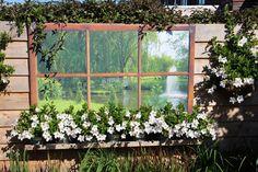 Geinig effect deze schuttingposter met venster om een houten frame gespannen. Net alsof het echte vensters zijn! De vensterbank met bloemen maakt het helemaal áf!