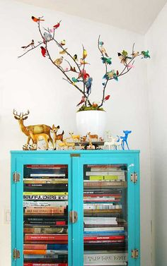 tree of ornamental birds, tiny deer collection and a curio filled with books ~ that's darling