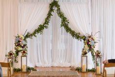 Indoor wedding ceremony decor, draped white fabric, garland, silver lanterns, colorful florals, see the full wedding feature on borrowedandblue.com // Key Elements