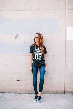 Acheter la tenue sur Lookastic:  https://lookastic.fr/mode-femme/tenues/t-shirt-a-col-rond-noir-et-blanc-jean-skinny-bleu-marine-baskets-basses-grises-lunettes-de-soleil-dorees/10559  — Lunettes de soleil dorées  — T-shirt à col rond imprimé noir et blanc  — Jean skinny bleu marine  — Baskets basses grises