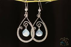 blue chalcedony - sterling silver-filled - length: 4.5 cm - width: 2 cm These blue chalcedony drops are framed in teardrop shaped silver wire-wrapped hoops. All metal components of these earrings are made from sterling silver filled wire. The stone drops are chalcedony, and
