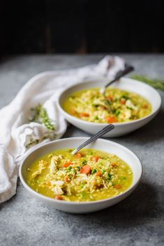 two bowls of chicken soup with couscous on a board