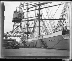 | MAGDALENE VINNEN berthed at number 2 wharf in Woolloomooloo, Sydney | This photograph depicts crew members with wool bales being winched on board the four-masted steel barque MAGDALENE VINNEN at number 2 wharf in Woolloomooloo, Sydney. The vessel sailed into Sydney Harbour on 27 February 1933, under the command of Captain Lorenz Peters. The barque was loaded with almost 16,000 bales of wool, the fourth largest shipment to have left Sydney, before it sailed the reco...