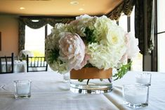 centerpiece: ivory hydrangea, polo roses and blush pink peonies. clear glass cylindars wrapped with a band of gold ribbon