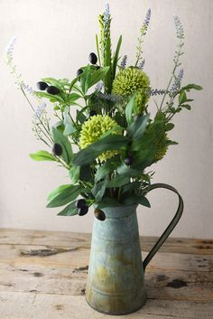 Wild Flowers, Olive Branches Water Can Arrangement. With a French countryside feel this is sure to add a beautiful and homey touch to your kitchen or living room