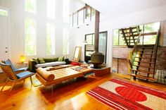 Modern loft style living space with hardwood floors, free standing vintage wood burning fireplace, red feature area rug, large windows, brick walls, wooden furniture, green sofa, and wooden staircase with black metal accents.