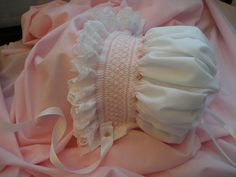 I This darling bonnet is made of easy care cotton batiste...smocked with DMC embroidery floss....adorned with seed pearls and handmade bullion roses. The bonnet ties with double sided satin ribbon and the ribbon at the back can be adjusted for further growth. I can custom make them bigger or smaller and your own color choice. Sizes are 0 - 3 months.....6 to 8 months and 8 to 12 months. This little bonnet would be perfect for that spring wedding....christening.... Sunday mornings or Photo…