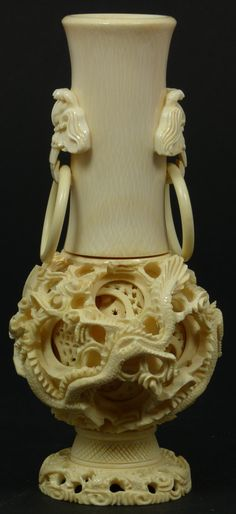 CHINESE IVORY DRAGONS CONCENTRIC BALL VASE  Chinese hand carved ivory concentric ball vase. Concentric ball has approx. 9 layers. Stunning dragon design to concentric ball and base. Neck of vase has foo masks with relief carved rings. 20th century.