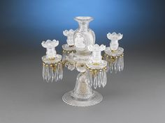 This exceptional and rare four-light cut glass centerpiece by the renowned Apsley Pellatt is a work of tremendous skill and artistry. A symphony of delicate diamond-cut glass, this light is topped with a flower vase center enclosing an intricate wheel-cut cameo, or sulphide, of Andromache, the wife of the Trojan Hector. Rosette accents, a conical stem and stepped circular foot complete this enchanting design. Apsley Pellatt glass featuring sulphides is very rare today